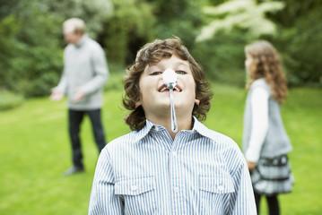 Boy balancing spoon on nose