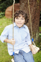 Boy swinging in backyard