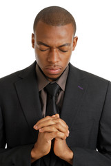 Business man praying with eyes closed