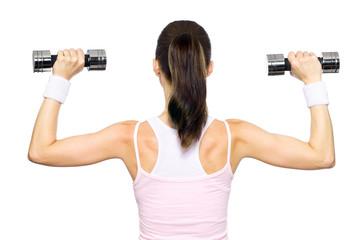 Sportliche junge Frau trainiert Rücken mit Hanteln
