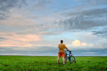 man with bicycle looking at skies
