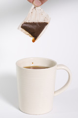 Tea bag being held out of cup