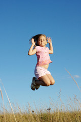 A girl makes a jump on grass in front of blue sky.