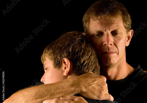 Father cries as he hugs son