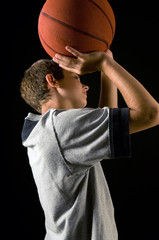 boy shooting basketball