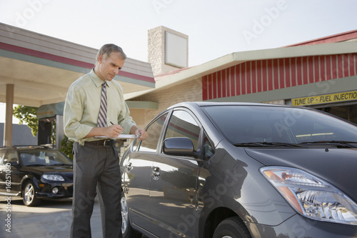 Insurance adjuster inspecting car