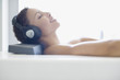 Woman listening to music in bathtub