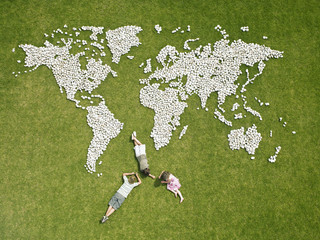 Children relaxing near world map made of rocks