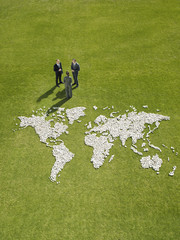 Businesspeople meeting near?world map made of rocks