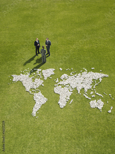 Businesspeople meeting near?world map made of rocks