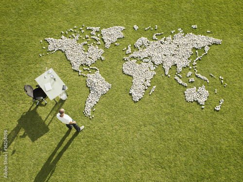 Businessman working near?world map made of rocks