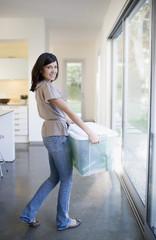Woman carrying bin of glass bottles