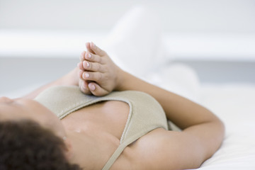 Woman laying on bed praying