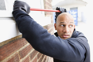 Burglar prying window open with crowbar