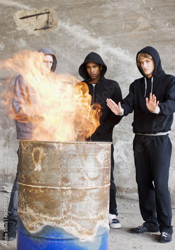 Men warming hands at fire in barrel