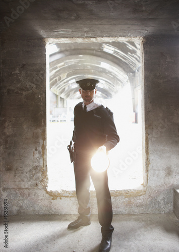 Security guard with flashlight checking bunker