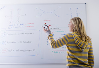 Teenage girl holding molecule model