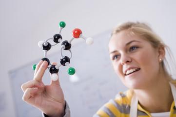 Teenage girl holding molecule model