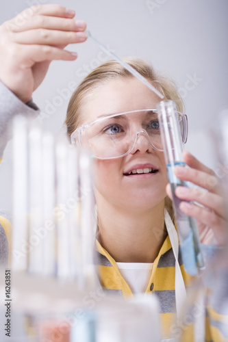 Teenage girl pouring liquid into test tube