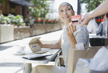 Woman paying for coffee with credit card