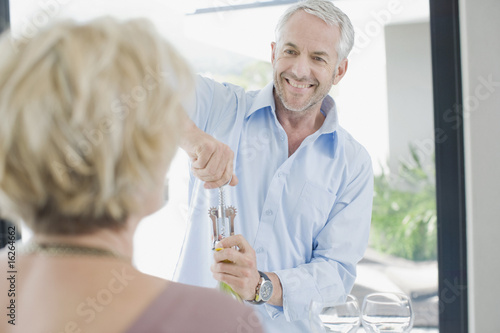 Man opening wine for wife