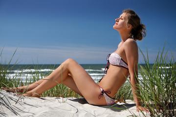 Beautiful girl enjoying the sun in dunes