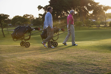 Men pulling golf carts on golf course