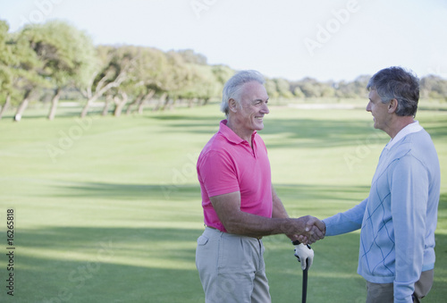 Men shaking hands on golf course