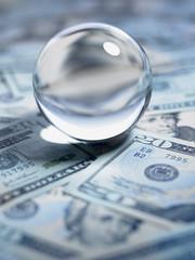 Close up of crystal ball on 20 dollar bills