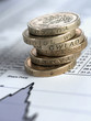 Stack of British pound coins on list of share prices