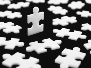 Scattered puzzle pieces with one piece upright