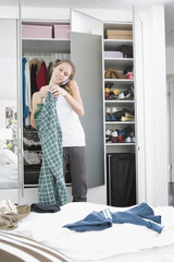 Teenage girl trying on clothes in bedroom and talking on cell phone