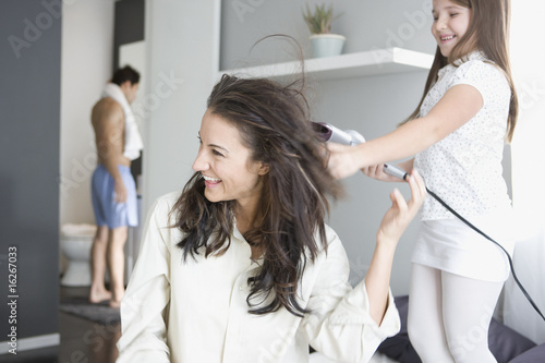 Girl blow drying mother?s hair
