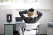 Businesswoman with hands behind head in office