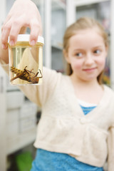 Girl looking at insect in jar in classroom