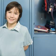 Boy standing near open school locker