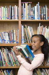 Girl carrying stack of books in school library
