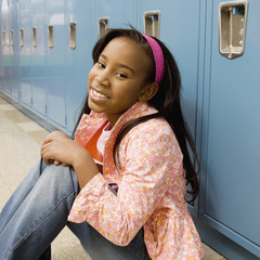 Girl sitting on floor in school hallway