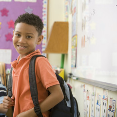 Boy with backpack in classroom