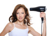 female drying her beautiful brunette hair with hairdryer