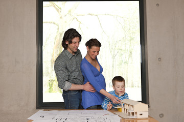 pregnant mother pointing to house model