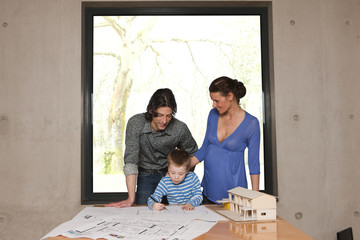 young man showing his family the plans for their new house