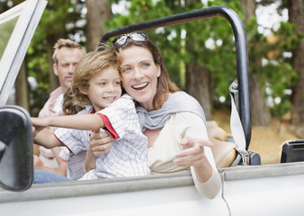 """""""Father, mother and son riding in jeep"""""""