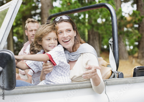 """Father, mother and son riding in jeep"""