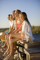 Family sitting on pier near beach