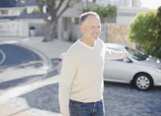 Man using keyless lock on car in driveway