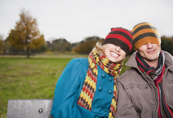 Playful couple in caps and scarves on park bench