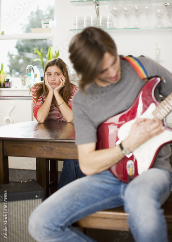 Bored wife listening to husband play guitar