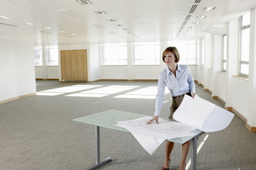 Businesswoman looking at blueprints in empty office