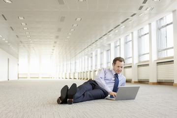 Businessman using laptop on floor in empty office